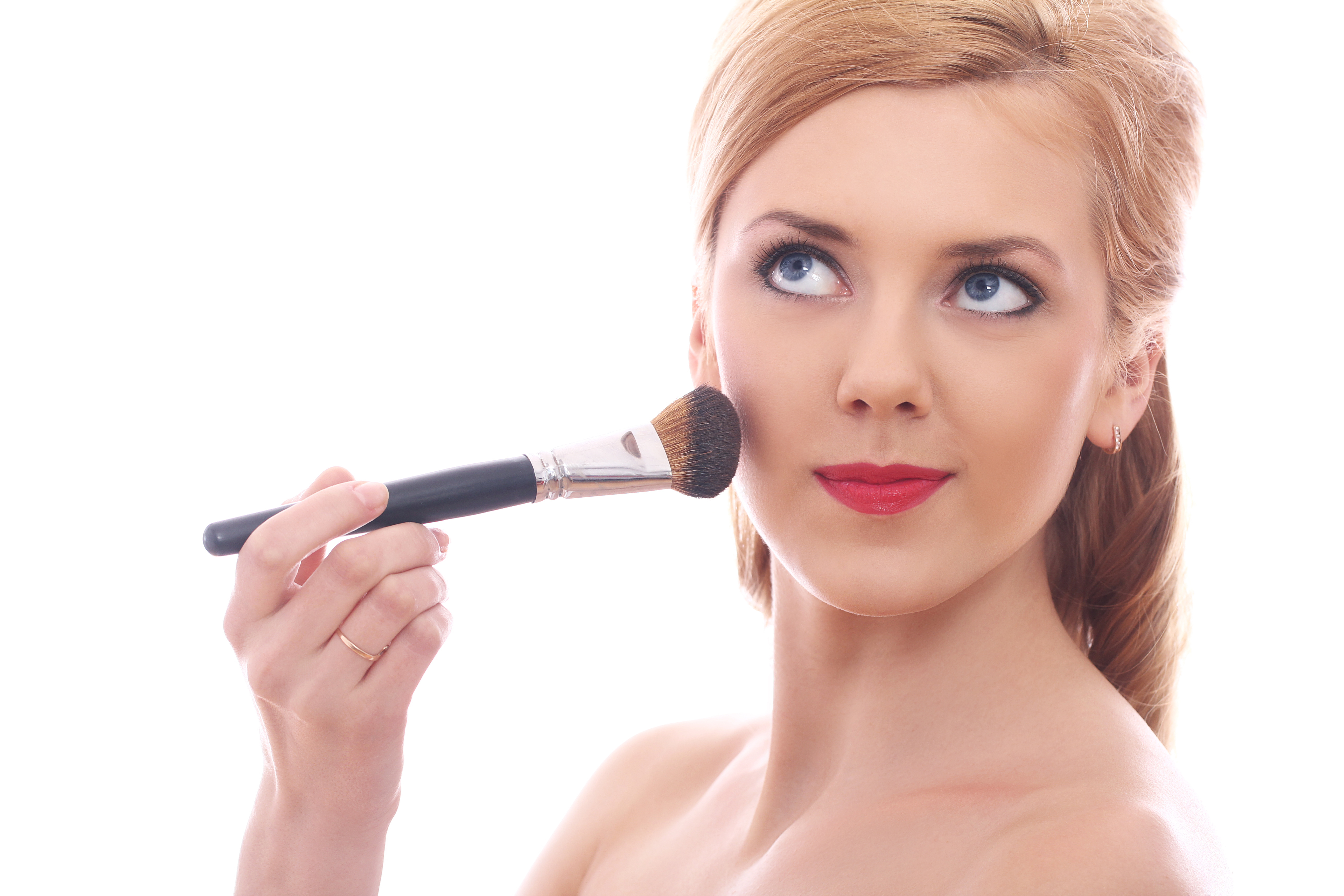 Beautiful woman applying make up with brush