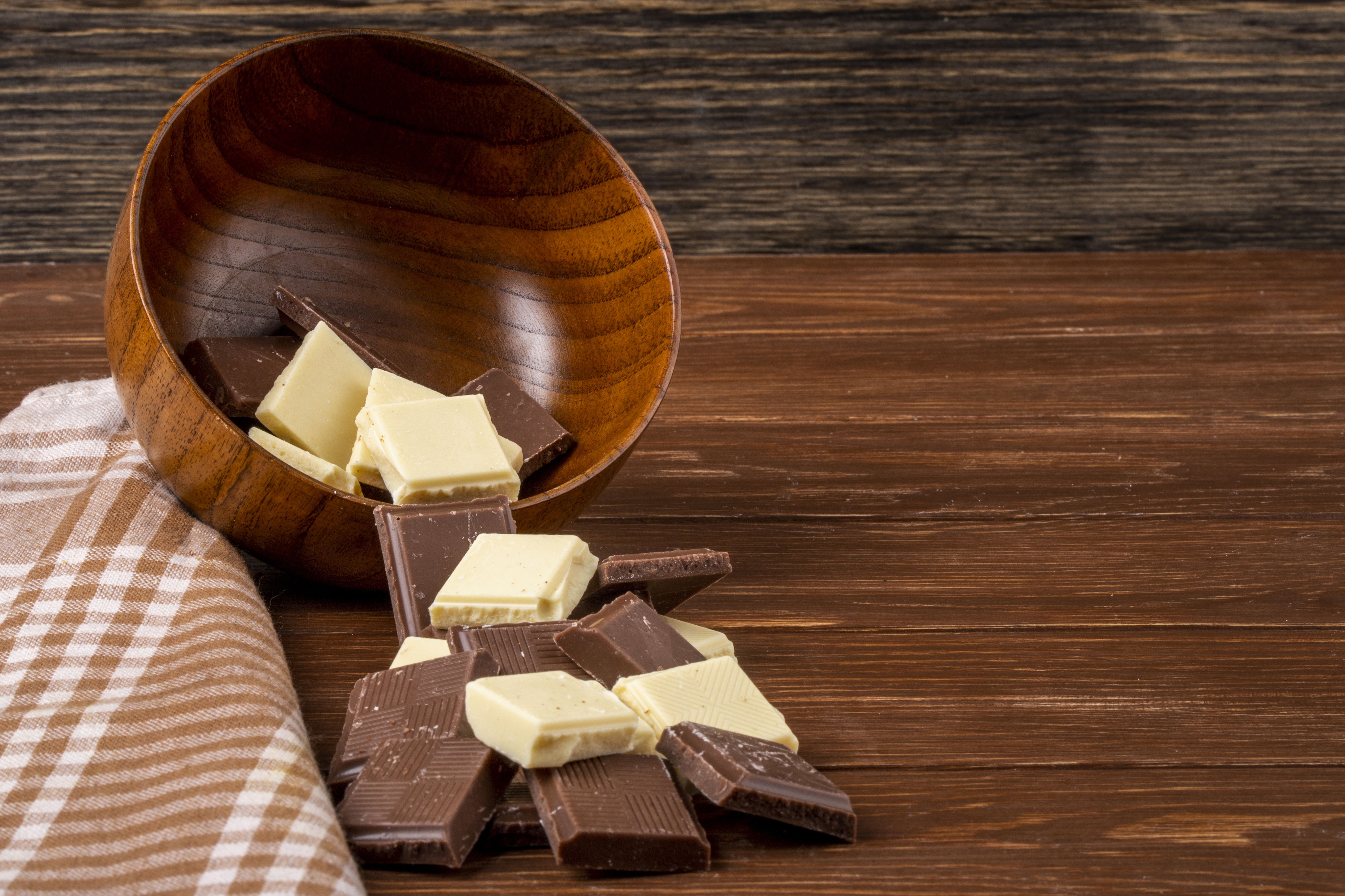 side view of dark and white chocolate pieces scattered from a wooden bowl on rustic background with copy space