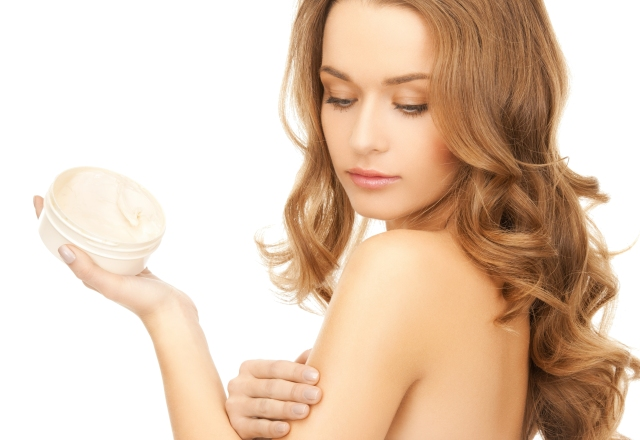 beautiful woman applying cream on her skin