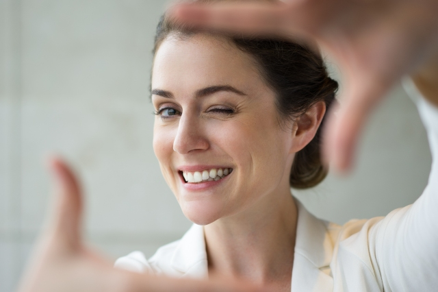 Closeup of Smiling Woman Making Frame Gesture